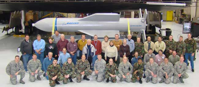 Weapon specialists gather in front of a mock up of the Massive Ordnance Penetrator and the B-2 weapons load trainer Dec. 18 at Whitman Air Force Base, Mo. Photo: USAF