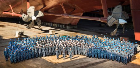 Shipbuilders take a photoop after completing the installation of the vessels' four propellers. All U.S. aircraft carriers procured since FY1958 have been built by Newport News Shipbuilding (NNS), of Newport News, VA, a shipyard that is part of Huntington Ingalls Industries (HII). NNS is the only U.S. shipyard that can build large-deck, nuclear-powered aircraft carriers. The aircraft carrier construction industrial base also includes hundreds of subcontractors and suppliers in various states. Photo: Huntington Ingalls Shipyards