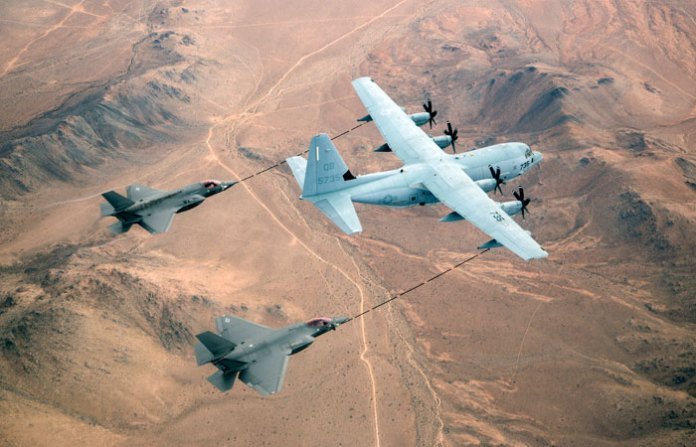 An F-35B (left) and F-35C (right) Lightning II fighters flying from Edwards AFB refuel from a USMC KC-130J tanker over the Mojave desert, Ca.