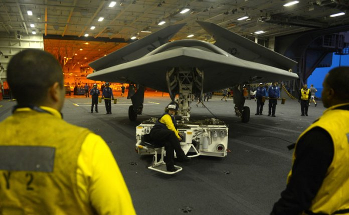 An X-47B Unmanned Combat Air System (UCAS) demonstrator is towed into the hangar bay of the aircraft carrier USS George H.W. Bush (CVN 77). (U.S. Navy photo by Timothy Walter)