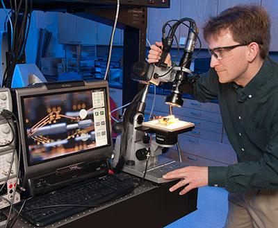 "Dr. Ronald Polcawich performs high-resolution imaging and testing of a millimeter-scale robotic leg structure. The roughly 3-mm-long leg consists of segments of piezoelectric thin-film actuators and thin-film copper sections designed to mimic the kinetics of a leg with a ""hip,"" ""knee"" and ""ankle"" joint sections. These ""legs"" have demonstrated the ability to move, lift (e.g., salt crystal in image), and resist impact into the silicon substrate. (Photo by Doug Lafon)"