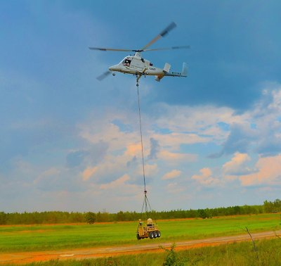 An SMSS carrying SATCOM and mast-mounted Gyrocam M9 stabilized EO sensor sling loaded by KMAX unmanned helicopter (the safety pilot is seated in for emergency only) Photo: Lockheed Martin