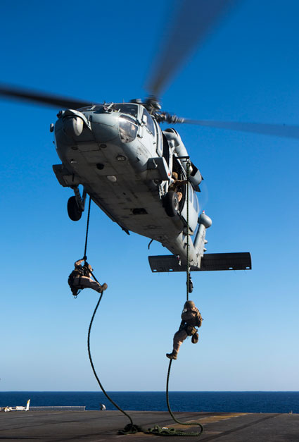 US Marines fast rope out of an SH-60 Seahawk with Amphibious Squadron 4 during fast rope training aboard the amphibious assault ship USS Kearsarge Nov. 5, 2015. U.S. Marine Corps photo by Cpl. Joshua W. Brown