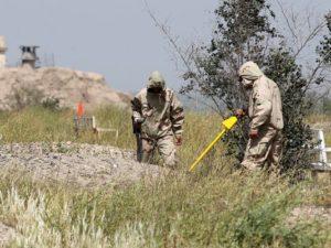 أفراد من القوات العراقية مختصون بنسف المتفجرات يبحثون عن عبوات ناسفة بدائية الصنع في مقبرة يُعتقد أنها تضم ضحايا مذبحة يونيو في مدينة تكريت. (صورة:  أحمد الربيعي/AFP/جيتي إيمدجز)