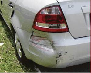 defensive driving dented rear wing on a grey car