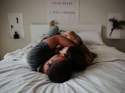 Duas pessoas abraçadas sobre uma cama.