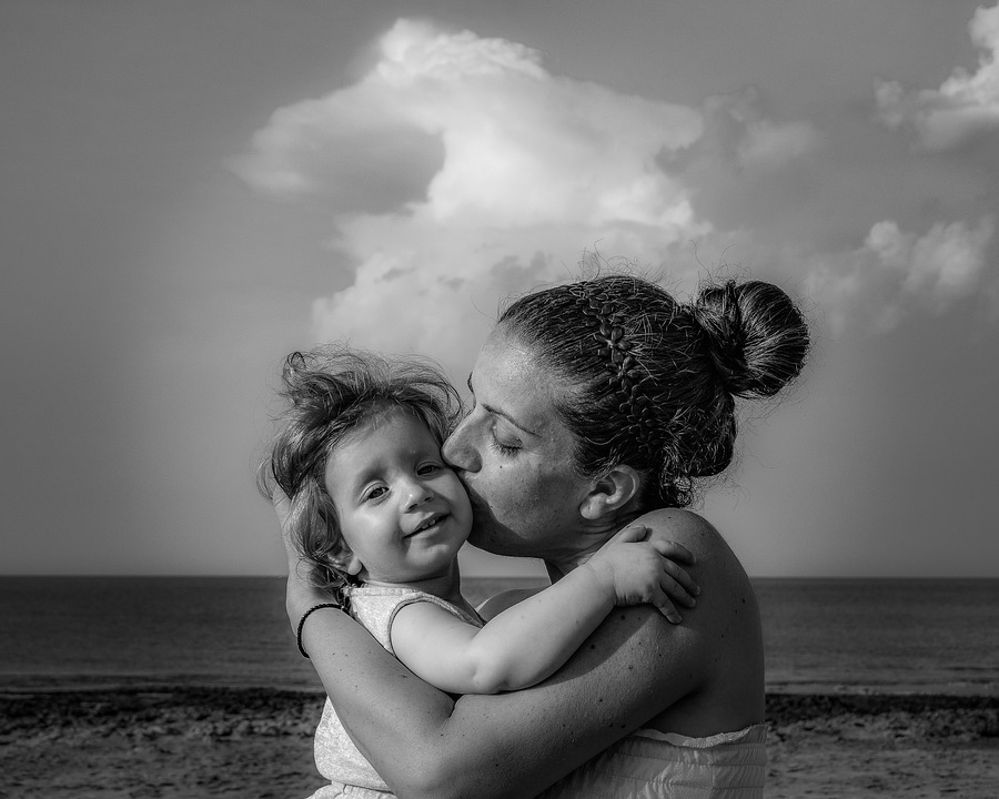 mother kiss baby on beach