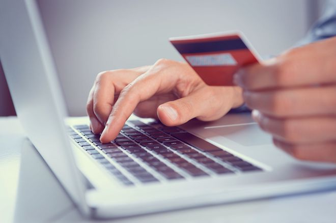 laptop hand holding payment card