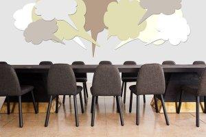 Des chaises dans une salle de réunion et des bulles de bandes dessinées au dessus de la table. Il n'y a personne autour de la table!