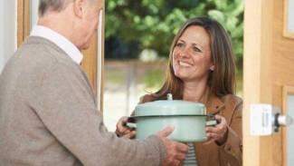 woman bringing meal dish to man