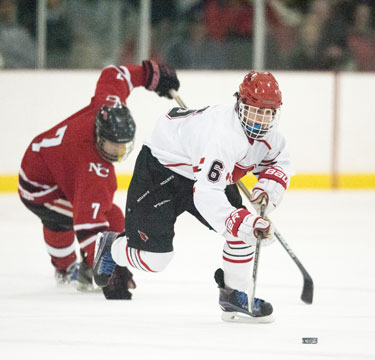 Greenwich High School's JT Lawrence works past his New Canaan opponent during Monday's game. (John Ferris Robben photo)