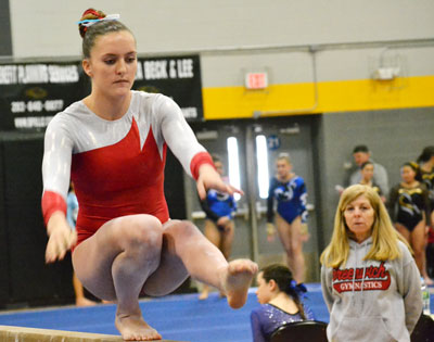 With head coach Sue Knight looking on, the Greenwich High School gymnastics team competes on the beam during the FCIAC championship meet. (Paul Silverfarb photo)