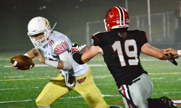 Greenwich High School quarterback Connor Langan gets chased down by a New Canaan defender during Friday night's game against FCIAC foe New Canaan High School. (Paul Silverfarb photo)