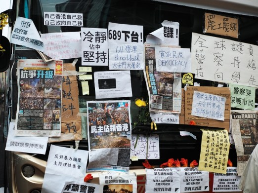 "A double decker bus that was trapped inside the occupied zone. ""Keep calm, Carry On"" ""689 (chief executive) steps down"" ""It's my HK and I will save it myself, Its my government and I will choose myself"" ""Support Students"" ""On Strike"" ""Oppose violent suppression, support peaceful assembly. ""Do you (Police) remember you took an oath to protect the citizens?"" ""Police needs to protect citizens"" ""Police, You are still supporting them? Go on strike instead!"" ""Please everybody keep calm and do not charge"""