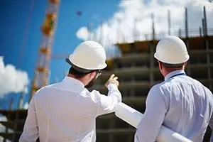 Architects point up at building at construction site