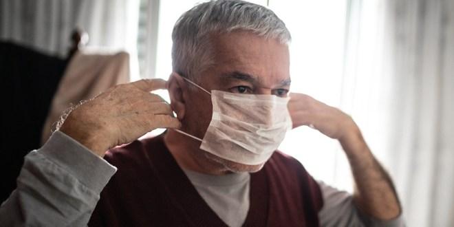 Älterer Mann, der zu Hause eine Schutzmaske für Coronavirus aufsetzt