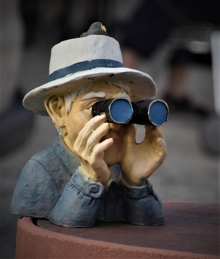 Figur eines älteren Menschen mit Hut, der durch ein Fernglas späht.