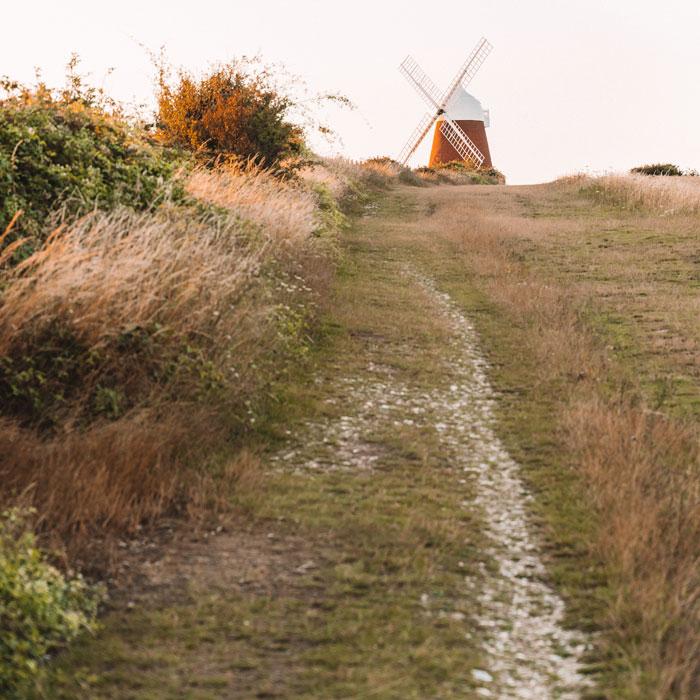 Am Ende eines grasigen Weges am Rand einer Hecke entlang wartet eine Windmühle in der Ferne.