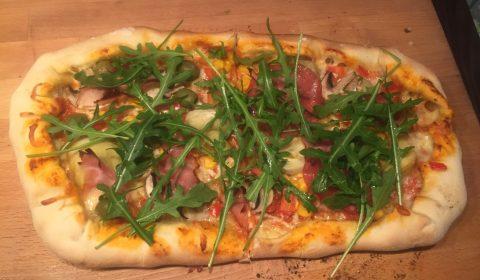 Pizza zum Schluss mit Rucola belegen