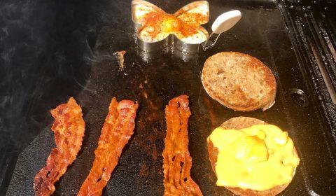 Ei und Bacon braten, Brötchen antoasten und den Käse schmelzen