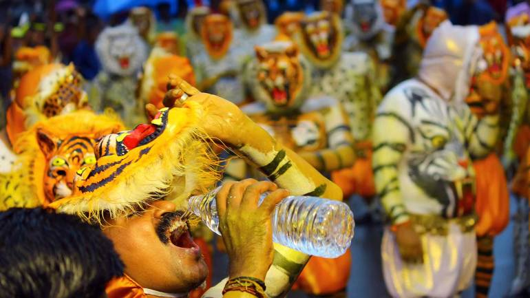 Puli-Kali-Pulikkali-A-participant-is-quenching-thirst