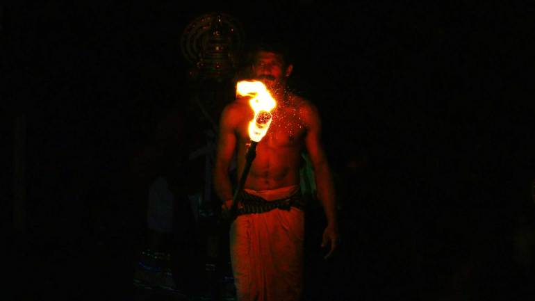 thookkam-performer-is-brought-to-the-shrine-of-Goddess-in-the-light-of-the-flaming-torch-according-to-custom