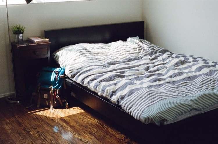 sebuah tempat tidur dengan bed cover warna biru