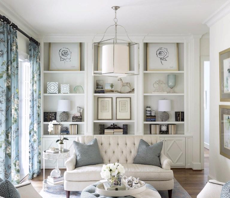 ruang tamu kecil dengan rak atau kabinet bertingkat setinggi dinding warna putih
