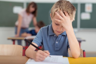 Kid in school stressed out by classwork