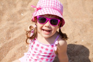 Little girl laughing and smiling at the beach wearing hat and sunglasses for sun protection