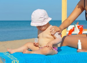 Baby in hat at the beach getting sunscreen applied by mother