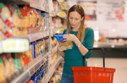 Shopping mother reads a nutrition label at the grocery store before purchasing