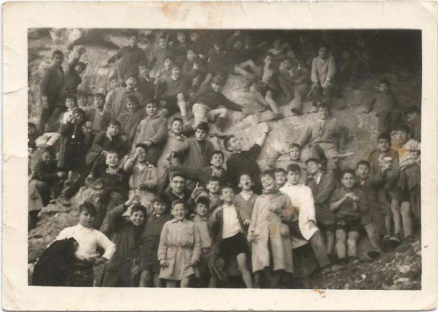 1962-63 Zuazo Esta foto está tomada en la boca de la cueva que hay en la margen derecha del Bayas, por encima de Aprikano; en ella destaca D. José Mª Eguizabal. Recuerdo casi todas las caras, pero no sus nombres; yo estoy en la primera fila saludando con la mano, a mi izquierda con el guardapolvo claro ceñido, un navarrico que creo que se llamaba Araya, , detrás de él José Mº Ibeas