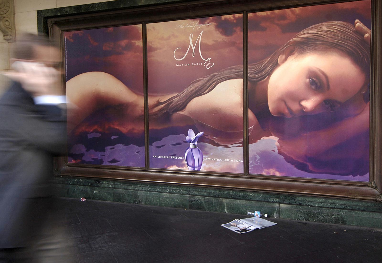 A man walks past an advertisement for perfume in Sydney, Australia. Photographer: Jack Atley/Bloomberg