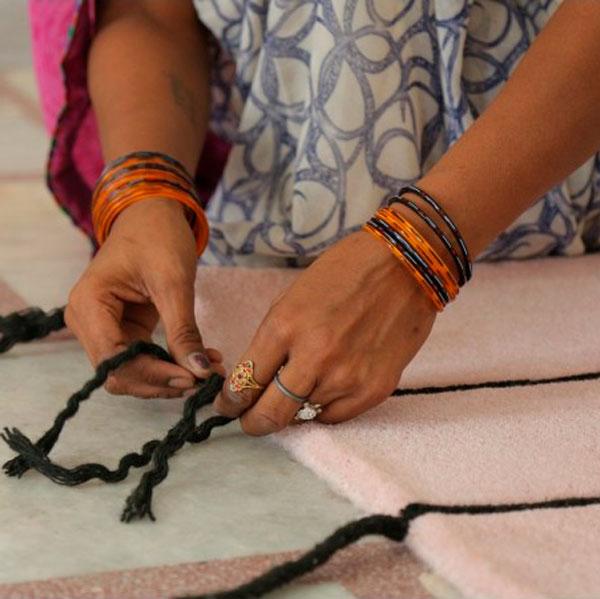Detalle de la fabricación artesanal de la alfombra de lana rosa Nordic Lines de Lorena Canals