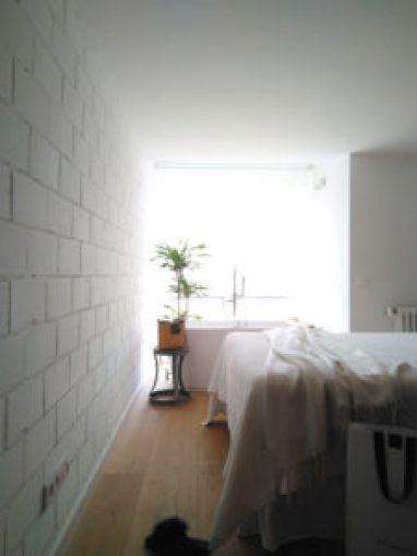 bañera exenta y pared de ladrillo en el dormitorio