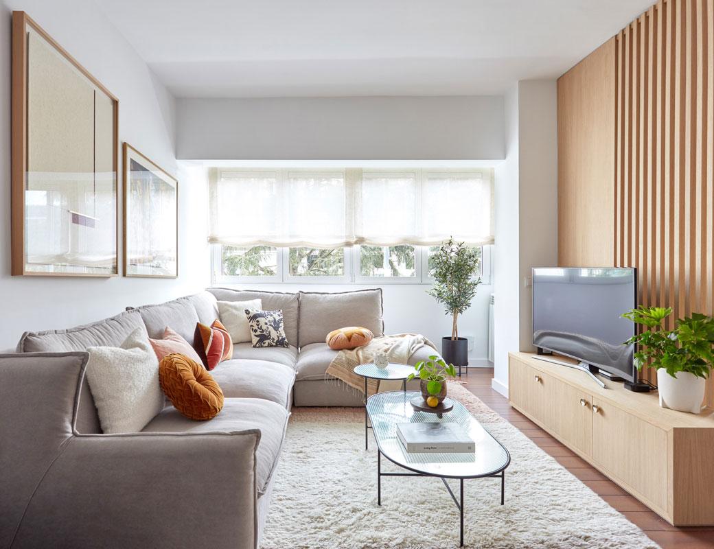 zona de estar con sofá rinconero y celosía detrás de la tele
