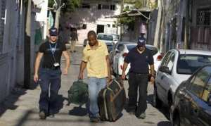 Israeli immigration officers escort an African migrant carrying luggage in south Tel Aviv June 13, 2012. (Photo: Reuters)