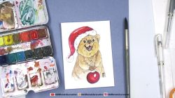 small brown furry marsupial with a red santa hat and xmas ball ornament
