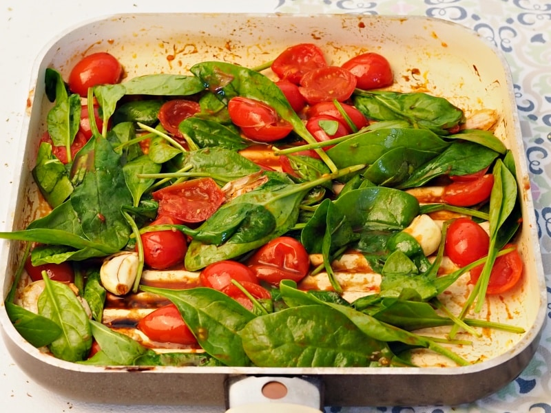 grill pan with spinach cherry tomatoes and garlic