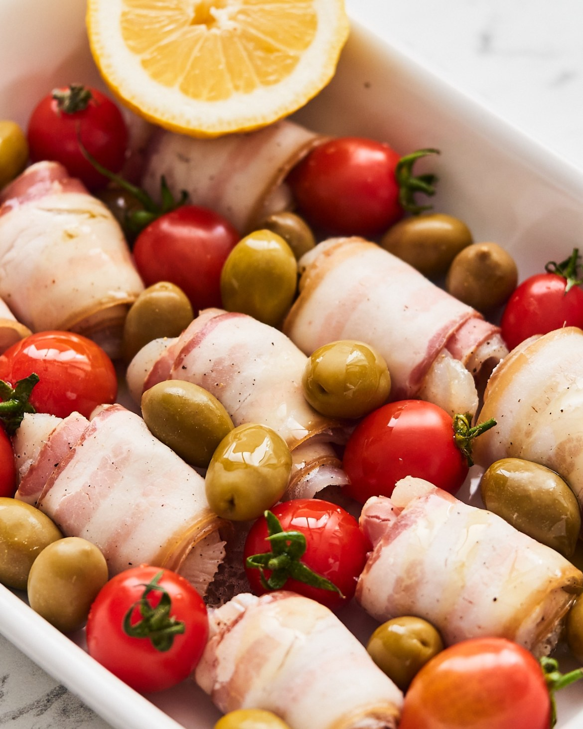 cod and bacon wraps with olives and tomatoes