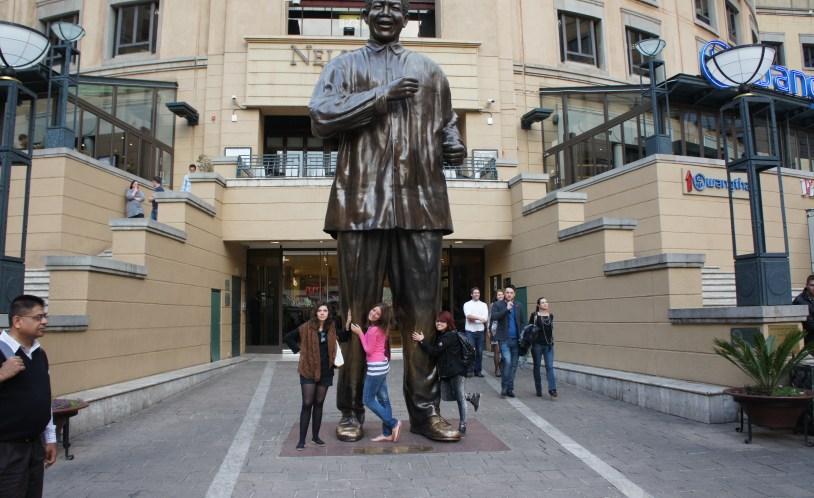 Jornalistas amando a estátua de Nelson Mandela, na praça que leva seu nome