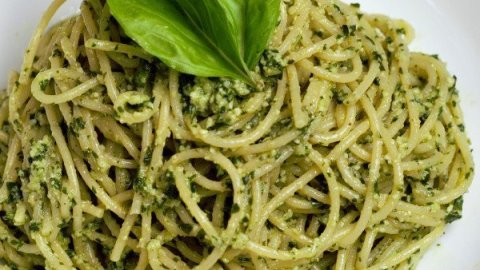 Bright green basil pesto on spaghetti with basil leaves in a white bowl.