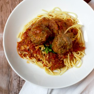Two meatballs sitting in Italian red sauce on top of cooked spaghetti in a white bowl.