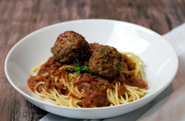 Two Italian Braised meatballs sitting in red sauce over spaghetti in a white bowl.