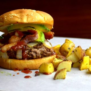 Barbecue Bacon Avocado Burger Stacked High and Served with Roasted Potatoes.