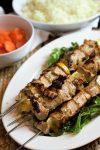 Beautifully grilled pork souvlaki skewers alongside glazed carrots and rice pilaf.