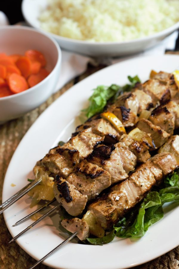 Beautifully grilled pork souvlaki skewers alongside glazed carrots and rice pilaf.