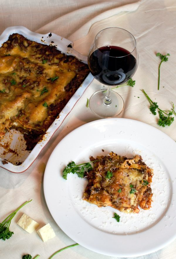 A big beautfiful piece of Classic Meat Lasagan and a glass of red wine.