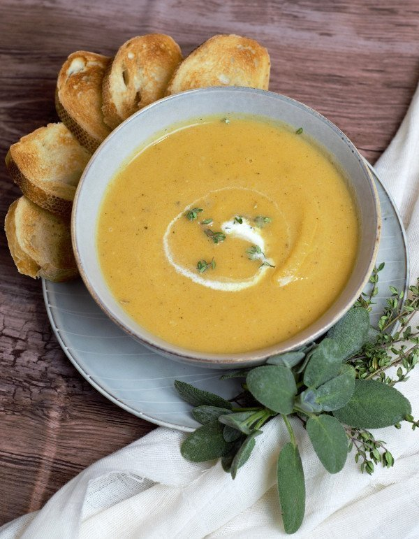 bowl of butternut squash soup surrounded by sage and crostini